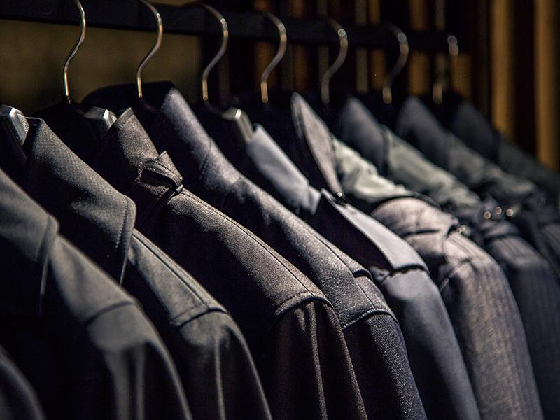 掛けられたスーツの生地を品よく見せる店舗デザイン